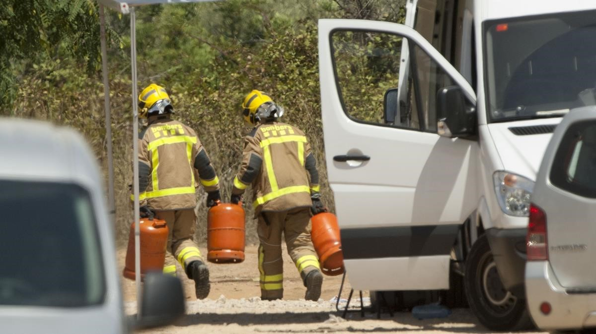 Los bomberos trasladan unas bombonas de butano halladas en el chalé de Alcanar. JOAN REVILLAS