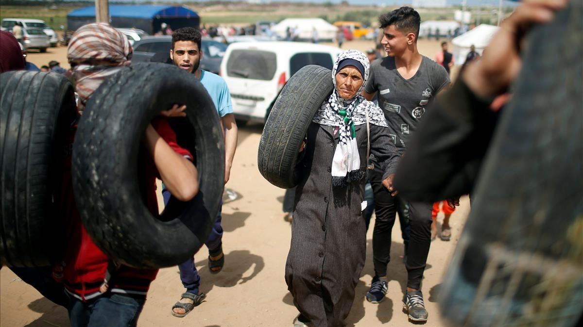 Manifestantes palestinos cargan con neumáticos mientras se preparan para las protestas en la frontera entre Gaza e Israel este lunes 14 de mayo.