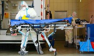 Miembros de los servicios de rescate muestran la forma de desinfectar una ambulancia para evitar la propagación del coronavirus, este jueves, en la ciudad alemana de Colonia.