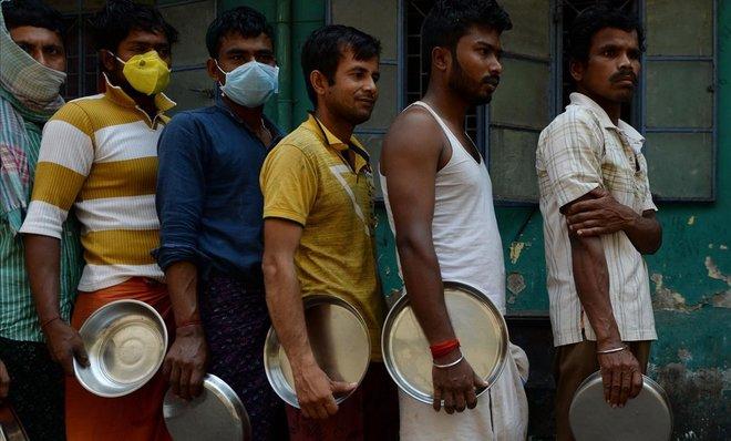 Migrantes con y sin máscaras forman cola para obtener alimentos proporcionados por una oenegé en la ciudad india de Chennai.