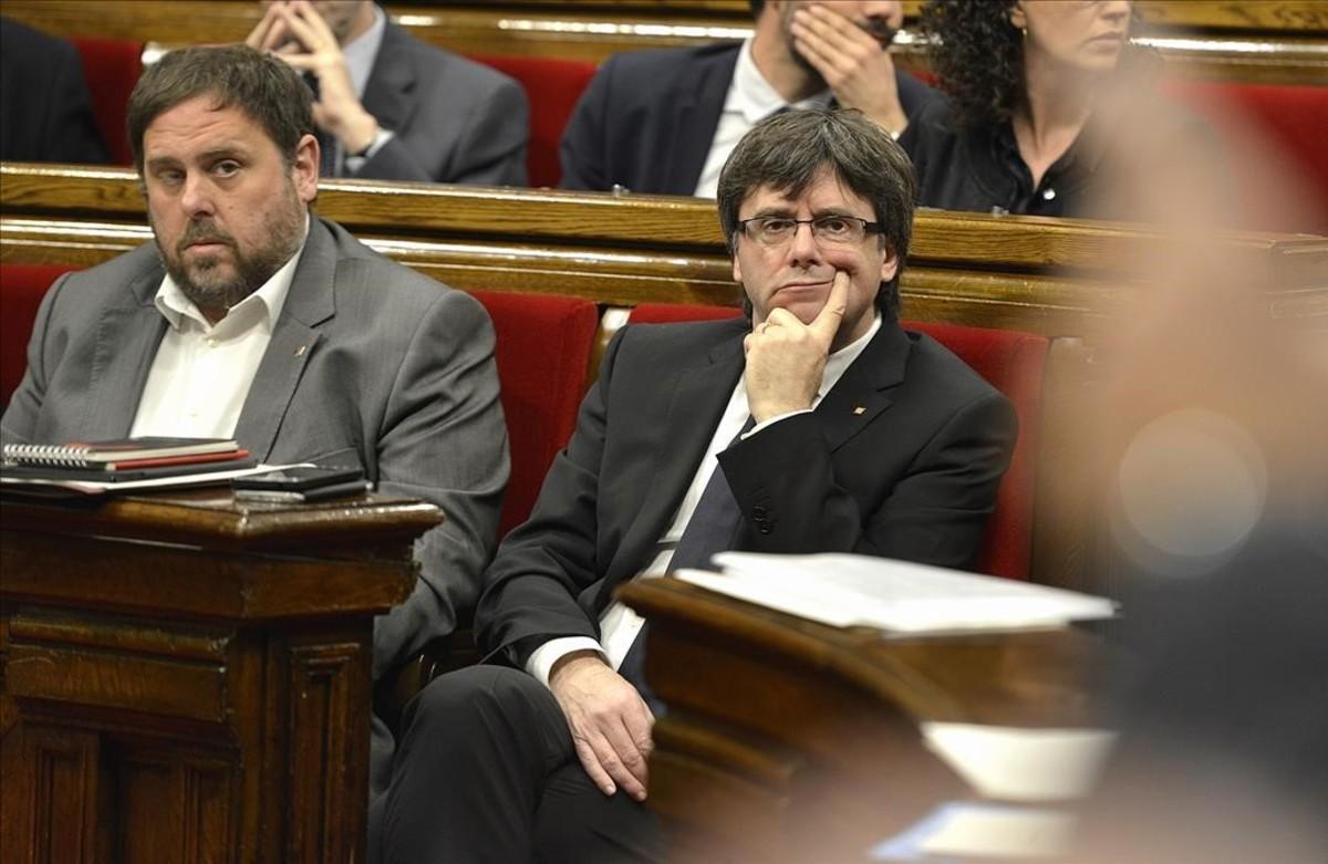 El 'president' Carles Puigdemont, junto al vicepresidente, Oriol Junqueras, en el Parlament.