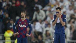 Piqué y Busquets se lamentan tras encajar el 2-0 del Madrid.