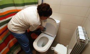 Una empleada doméstica limpia el baño de una vivienda en Figueres.