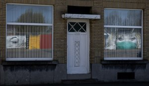 El reflejo de un mural de arte callejero, que representa a un trabajador de la salud con una máscara facial del artista callejero belga CAZ, aparece en la ventana de una casa de Wetteren (Bélgica).