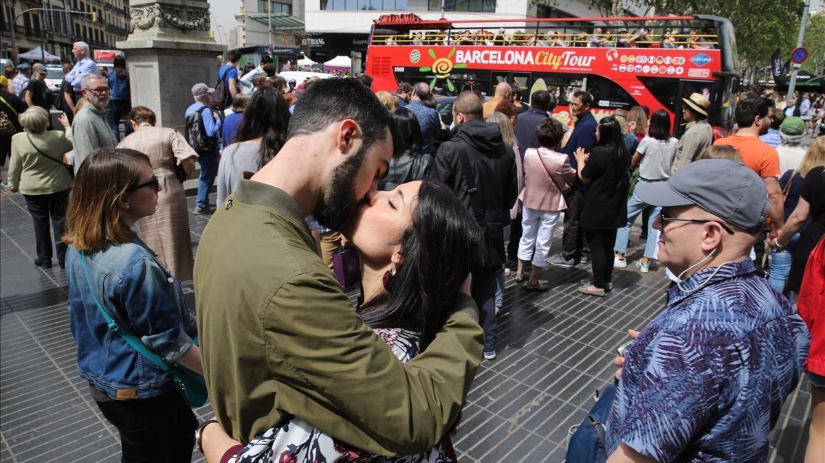 Una pareja de enamorados besándose en la plaça de Catalunya.