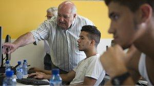 Una persona jubilada enseña de forma voluntaria informática a jóvenes, en La Roca del Vallès.