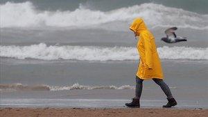 Una persona pasea por la playa de la Malvarrosa bajo el temporal.