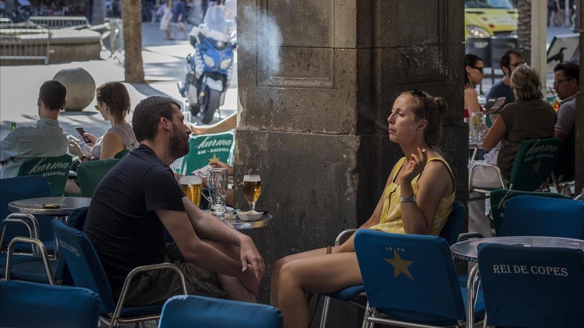 Una persona fuma en una terraza de la plaza Reial.