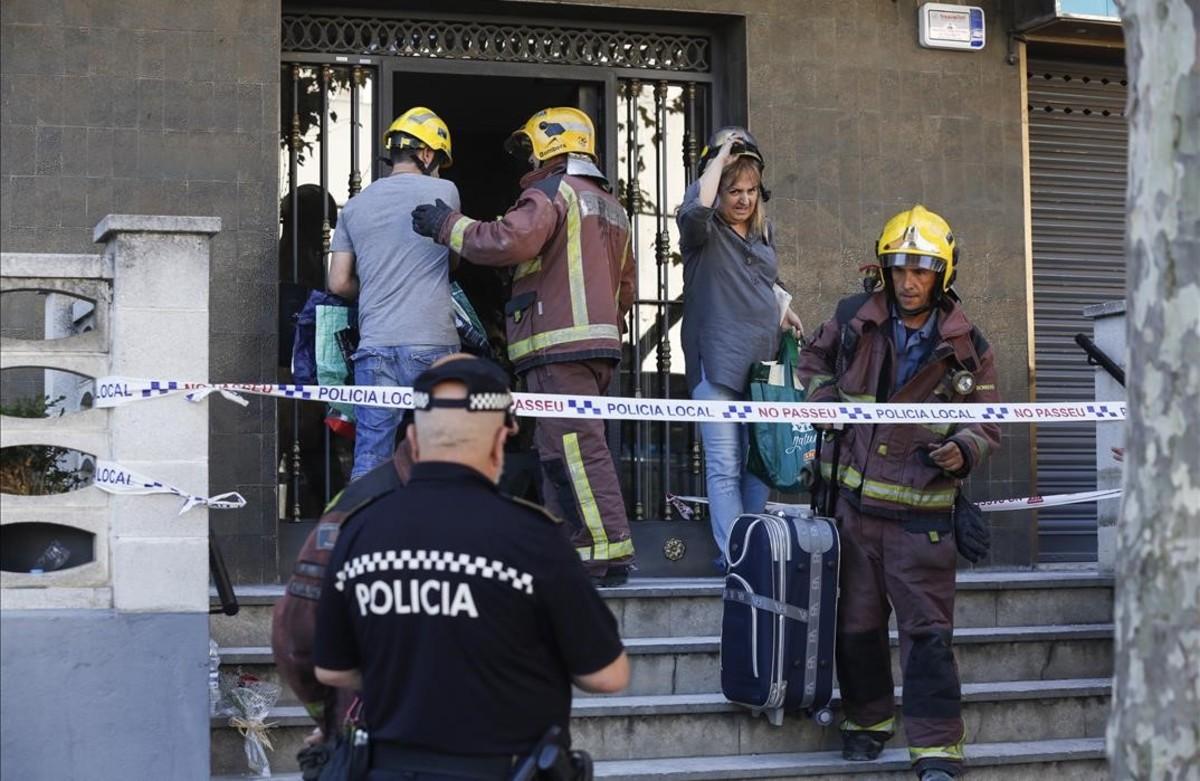 Uno de los vecinos sube acompañado por un bombero a su vivienda para recoger algunas pertenencias personales.