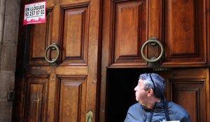 Un vecino observa un letrero que avisa de un ático en alquiler en su propio bloque.