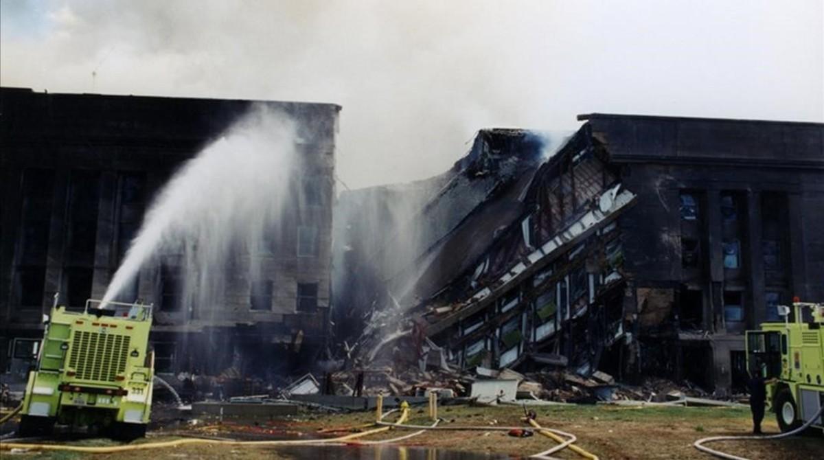 Los bomberos tratan de extinguir el fuego originado despues de que el vuelo 77 de American Airlines impactase contra las instalaciones del Pentagono.