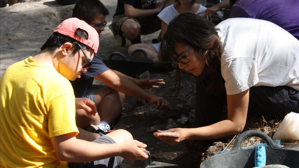 Chicos y chicas con síndrome de Down participan en una excavación en Les Guixeres de Vilobí, en agosto del 2017.