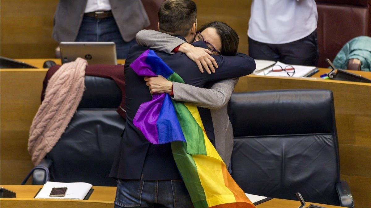 Oltra y el diputado Ferri se abrazan tras la aprobación de la ley.