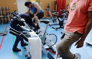 Marc ayudando un paciente en una de las bicicletas estáticas del gimnasio del Institut Guttman