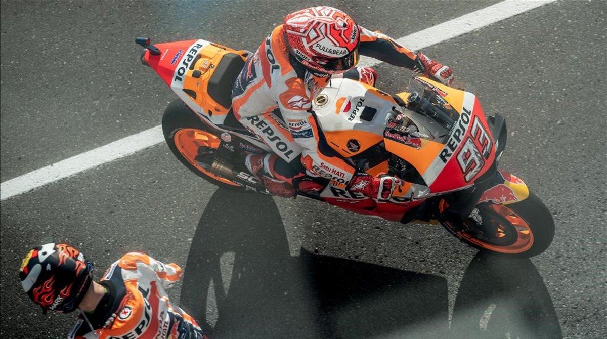 No me digan que la foto no es curiosa.Marc Márquez llega al boxe del equipo Repsol Hondajusto en el momento en que su nuevo companero,Jorge Lorenzo,sale a coger su RC213V.