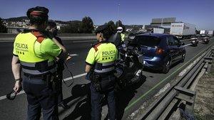 Dos agentes de una patrulla Espiell paran a un motorista que ha cometido una infracción. Delante, el coche policial camuflado.