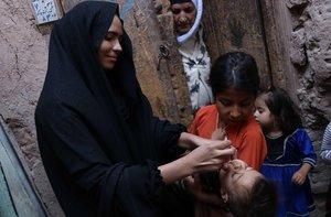 Unos trabajadores sanitarios visitan un hogar para administrar una vacuna contra la polio a los niños en la ciudad de Herat (Afganistan)