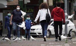 Una familia, protegida con mascarillas, pasea por una calle.