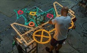 Un operario revisa las bombillas de una instalación para la campaña de luces de Navidad de Barcelona