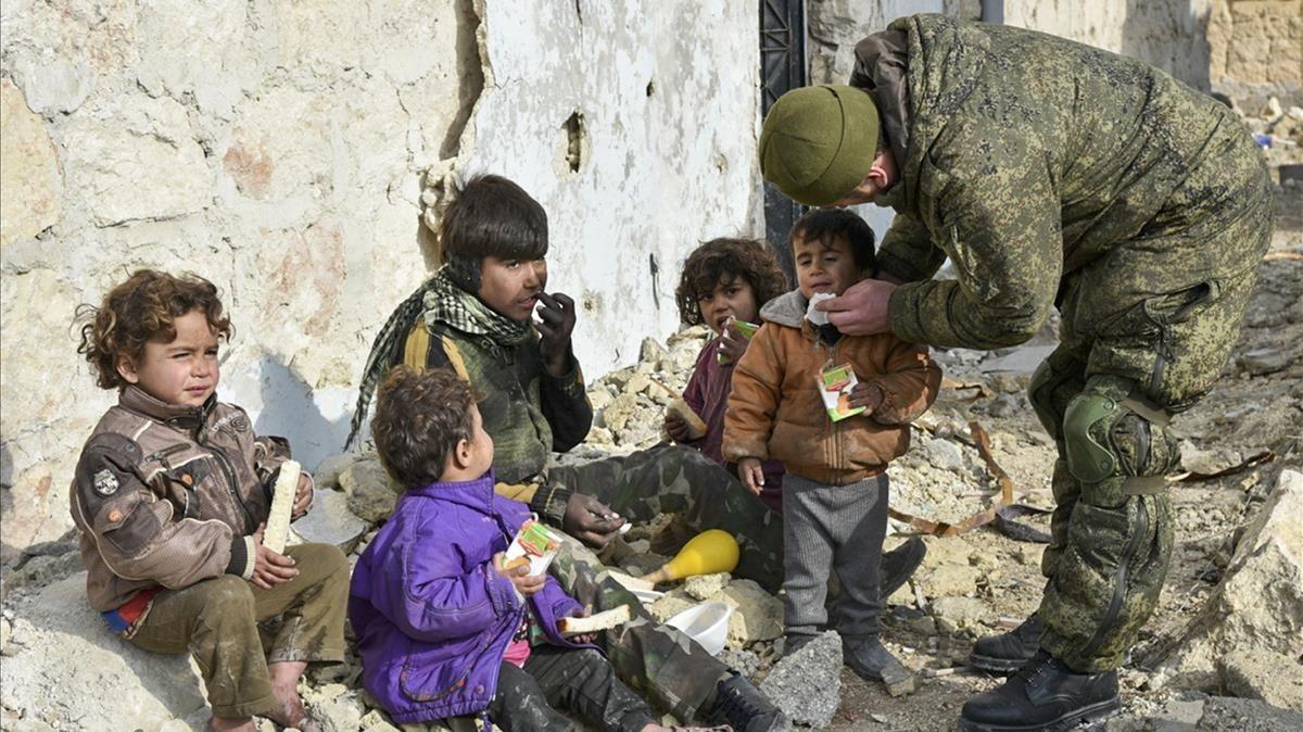 Un militar ruso entrega supuestamente zumo de frutas a niños de Alepo (Siria), en una imagen sin fecha distribuida por el Ministerio de Defensa ruso.