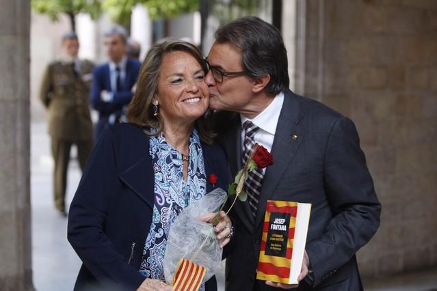 Artur Mas y su esposa, Helena Rakosnik, se intercambian una rosa y un libro.