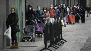 Colas de gente con mascarillaen un supermercado de l'Hospitalet de Llobregat, esta mañana.