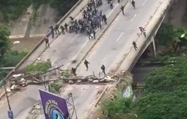 La policía venezolana irrumpe, en motos, para dispersar una manifestación.
