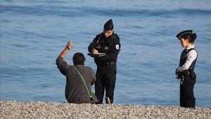 Dos agentes de policía local de Niza multan a un hombre por estr en la playa, este viernes.