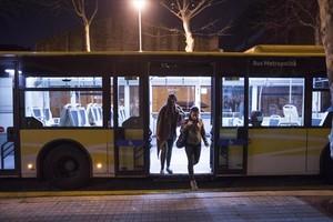 Dos personas bajan de un autobús de la línea nocturna N8.
