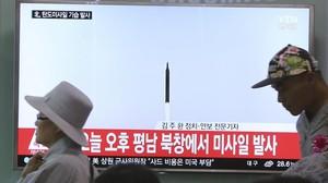 Dos personas pasan ante una pantalla de televisión donde se muestran imágenes de archivo de un lanzamiento de un misil por parte de Corea del Norte, en la estación ferroviaria de Seúl (Corea del Sur), el 21 de mayo.