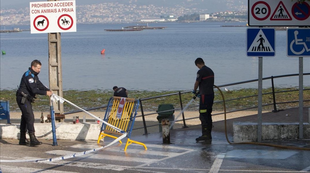 Operarios limpian el lugar donde el joven fue asesinado, en la playa deArealonga de Chapela, en Redondela, Vigo.