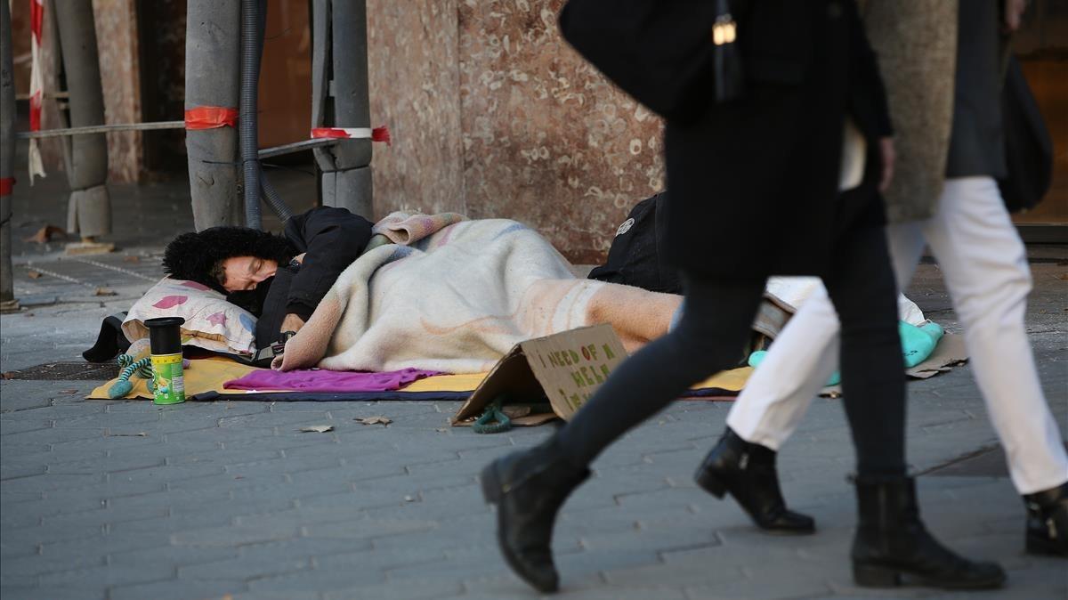 Un hombre duerme en Paseo de Gràcia, el pasado mes de noviembre.