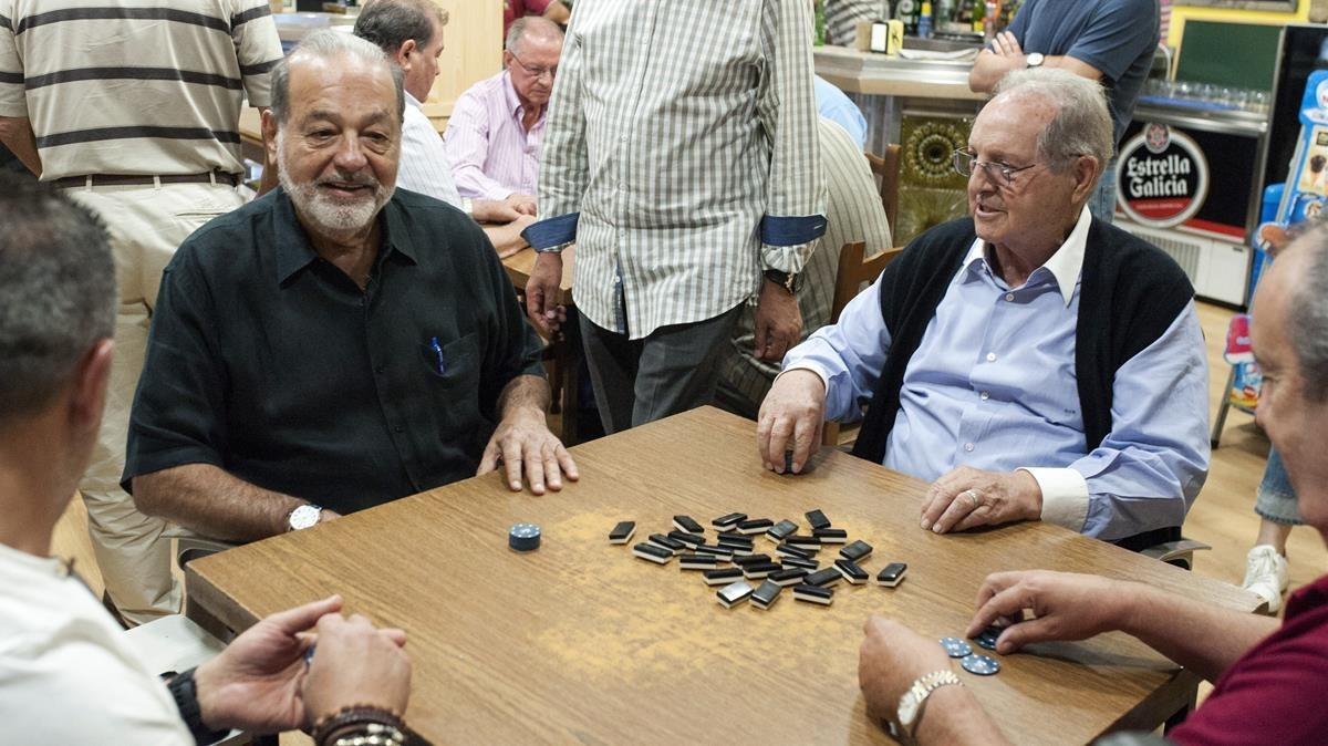 Los empresarios Carlos Slim (izquierda) y Olegario Vázquez, este martes, jugando al dominó en un bar de Avión (Ourense).
