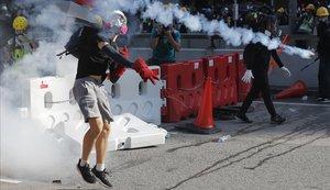Un manifestante lanza un bote de gas lacrimógeno durante las protestas con motivo de la huelga general en Hong Kong.