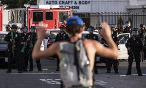 Un manifestante protesta ante varios policías, en Los Ángeles.