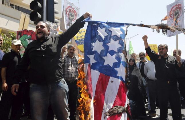 Manifestantes iranís queman una bandera estadounidense mientras piden la liberación de Palestina.
