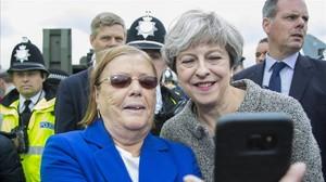 May (derecha) posa para un selfi con una asistente a una exhibición militar en Liverpool, el 24 de junio.