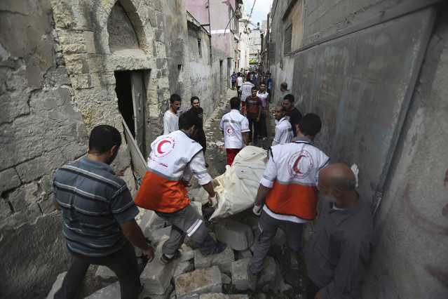 Médicos palestinos evacúan un cadáver en el barrio de Shayahía, este domingo.