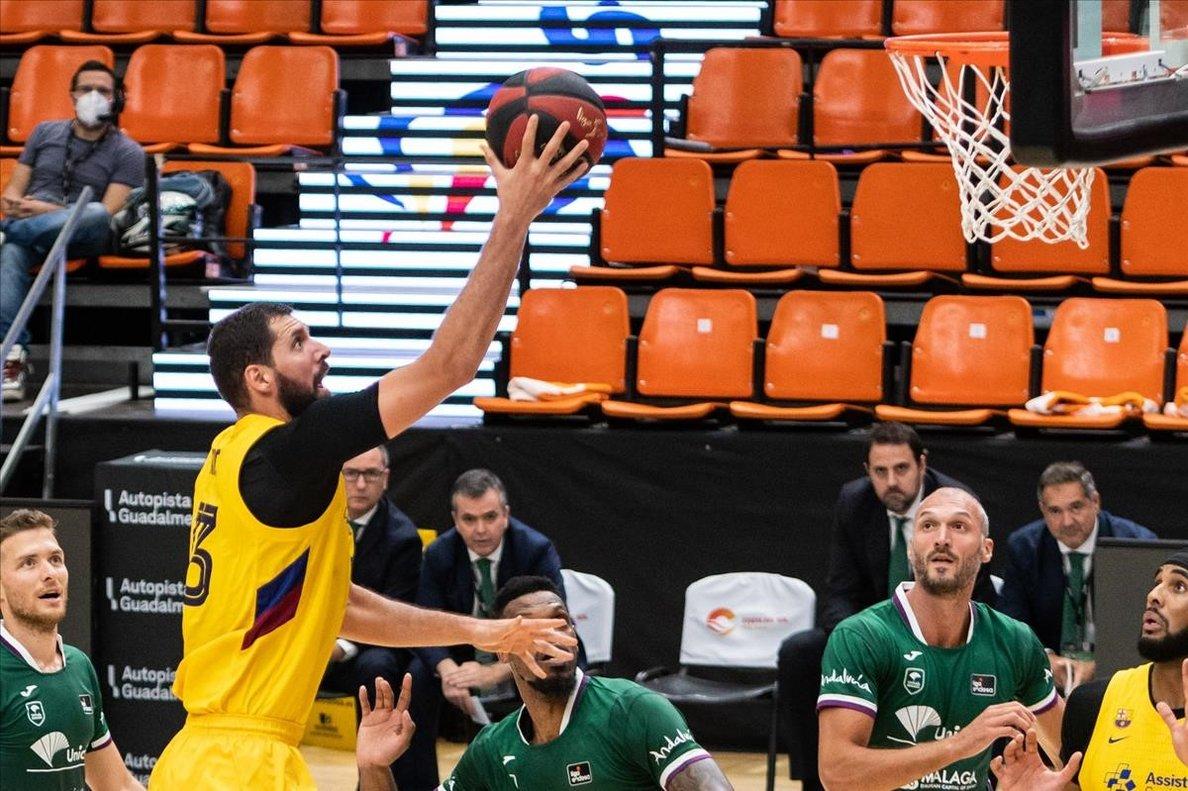 Mirotic deja una bandeja ante la mirada de varios jugadores malagueños