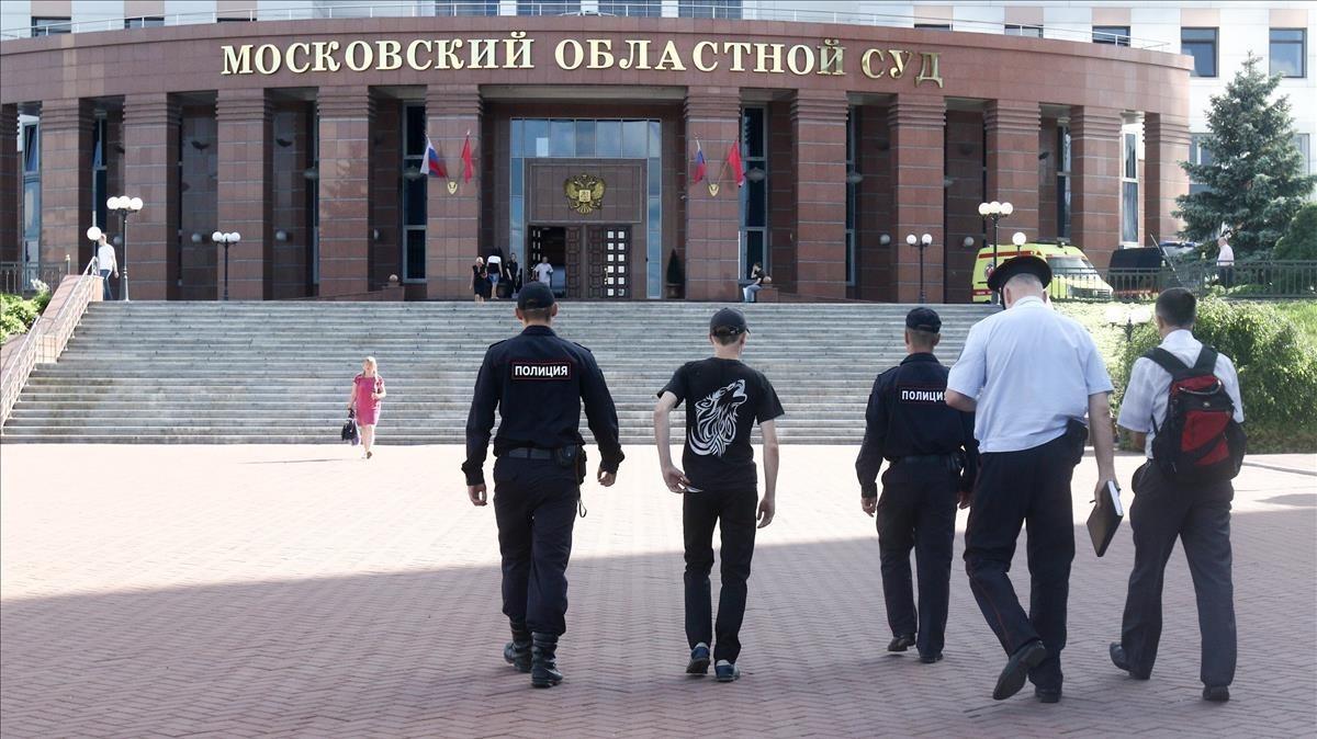 Varios policías caminan hacia el edificio de los juzgados donde se ha registrado el tiroteo.