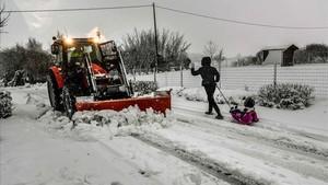 Un niño tirado porun trineo pasa delante una máquina quitanieves en Godewaersvelde el norte de Francia.