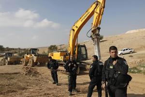 Policías israelís montan guardia junto a excavadoras tras demoler las casas del poblado beduino de Um al Hiran, este miércoles.