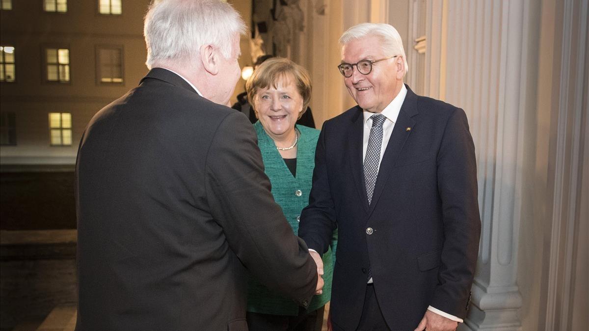 El presidente alemán, Frank-Walter Steinmeier (derecha) saluda al primer ministro bávaro y presidente de la CSU, Horst Seehofer (izq), junto a la cancillera Merkel, en Berlín, el 30 de noviembre.