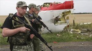 Rebeldes prorrusos armados, al lado del fuselaje del avión derribado, en julio de 2014.