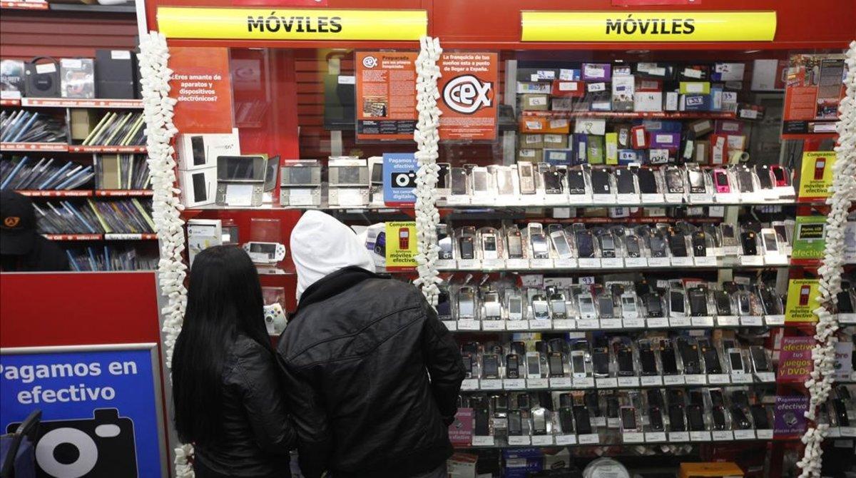 Dos jóvenes, en un establecimiento de venta de artículos electrónicos.
