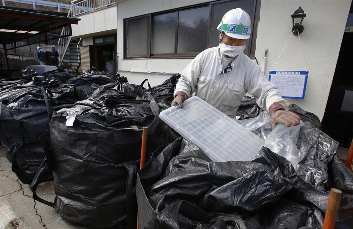 Un trabajador mete en una bolsa residuos radiactivos en una casa de Minamisoma.