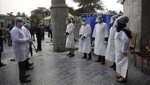 Trabajadores sanitarios esperan toman la temperatura a los asistentes a un acto oficial, el pasado 9 de marzo en Kabul.