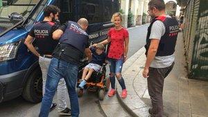 Tres agentes de los Mossos entregan la silla de ruedas robada a sus propietarios, en Sant Andreu