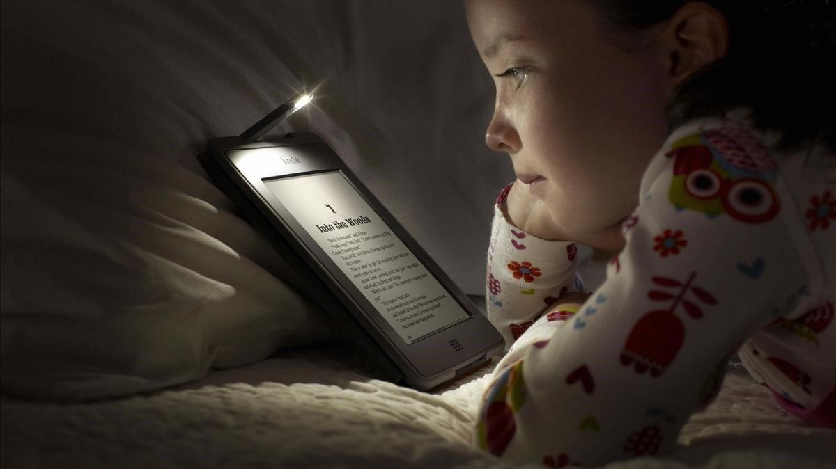 Una niña lee en un Kindle Fire Touch de Amazon.