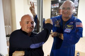 Los astronautasScott Kelly (con traje espacial y gafas) y Mark Kelly (con bigote) unos días antes del despegue de la misión espacial